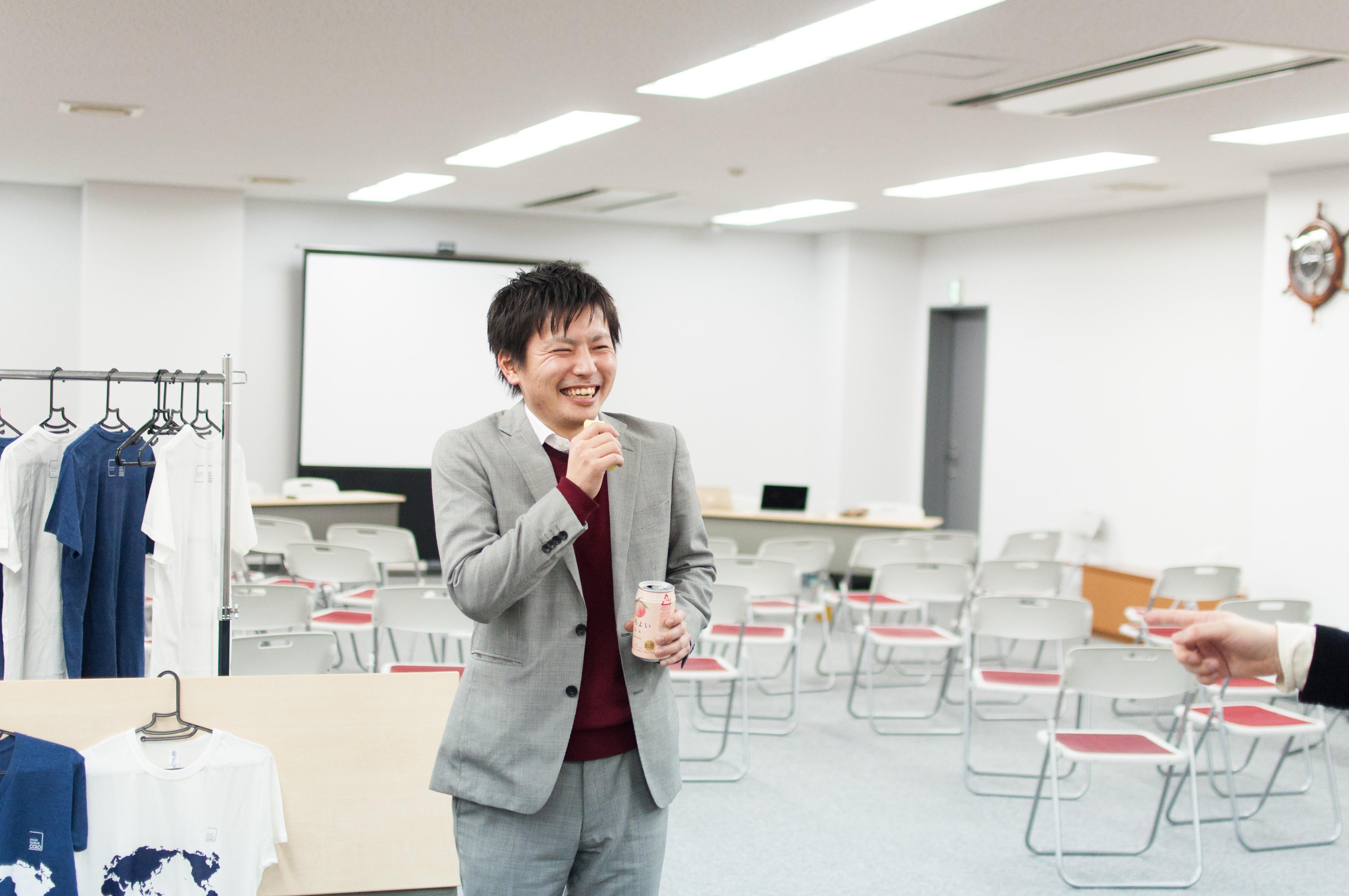 福島県の名物お土産「ままどおる」をマイクに見立て、桃のお酒を片手に、締めの挨拶に挑むおちゃめな菅家さん。